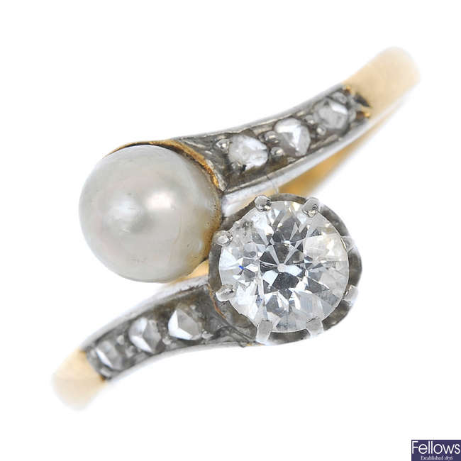 An early 20th century silver and 18ct gold diamond and cultured pearl two-stone crossover ring.