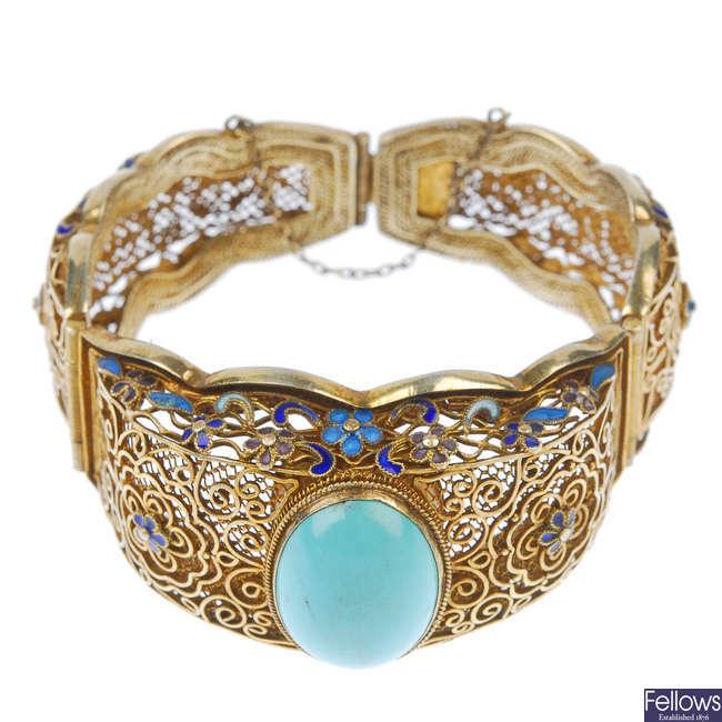 A gilt enamel and turquoise hinged bangle.