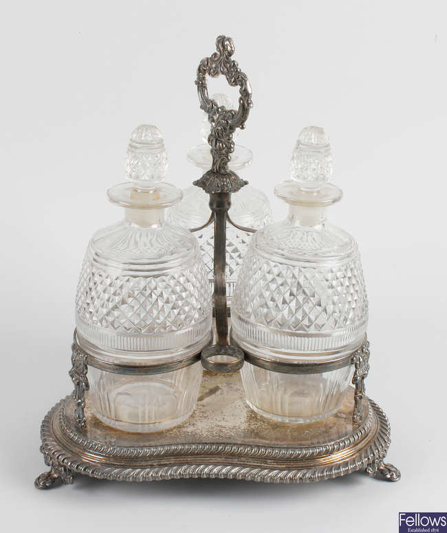 A silver plated stand holding three glass decanters, etc.
