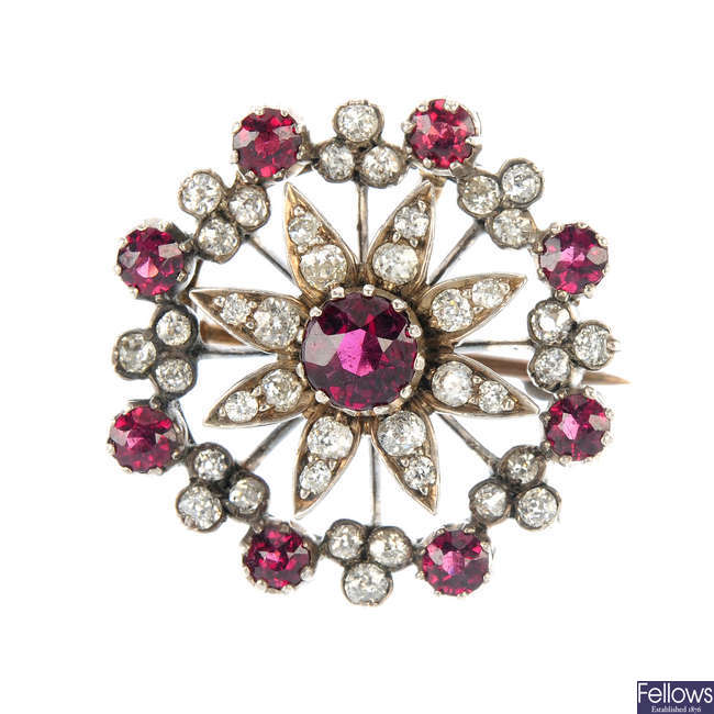 A late 19th century silver and gold, garnet and diamond floral brooch.