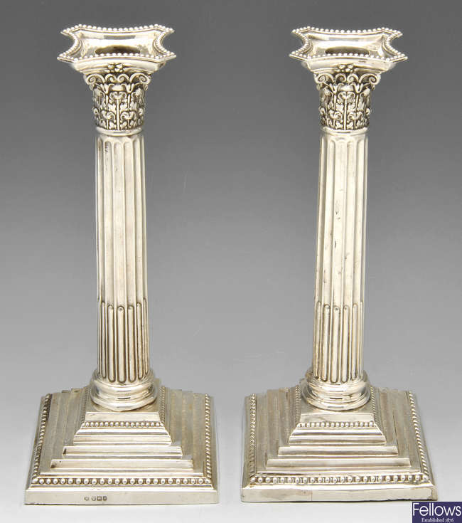 A pair of late Victorian filled silver candlesticks.