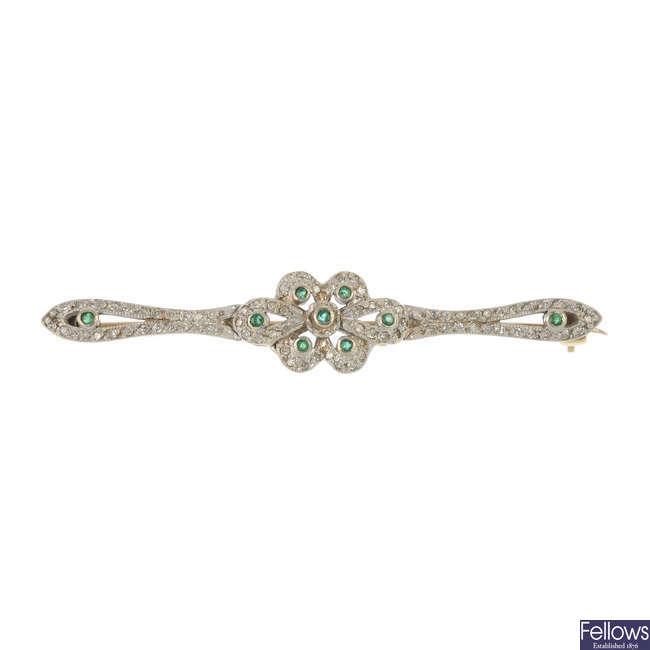 A diamond and emerald bar brooch.