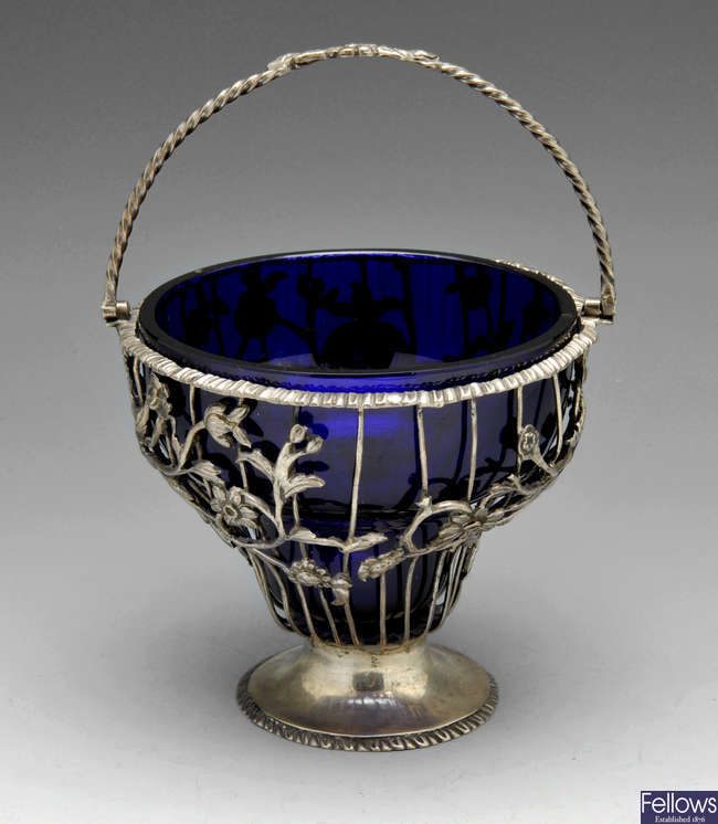 A George III silver swing handled sugar basket with blue glass liner.