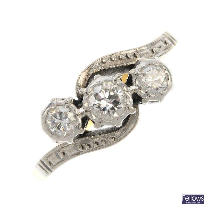 A mid 20th century platinum and 18ct gold diamond three-stone crossover ring.