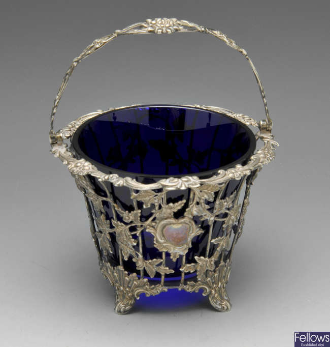 A Victorian silver basket with blue glass liner.