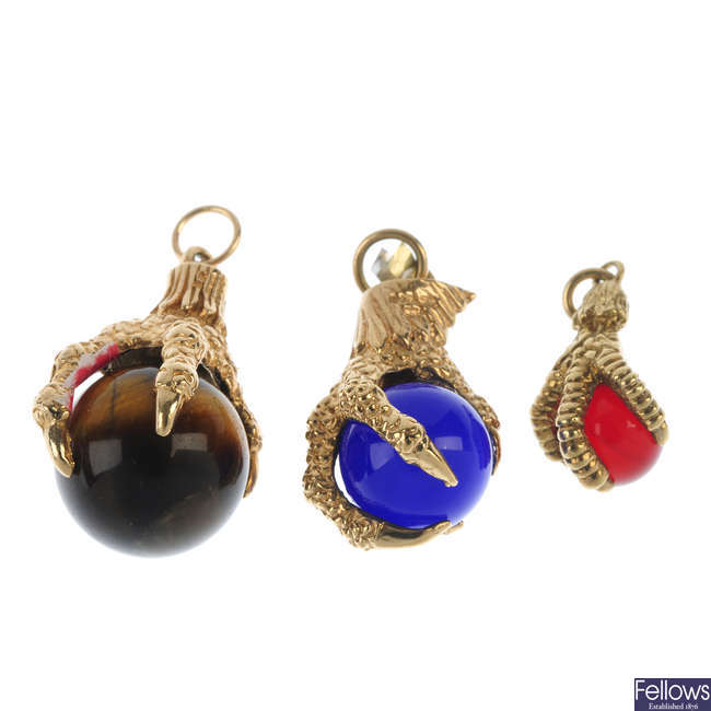 A group of three gem-set claw pendants.