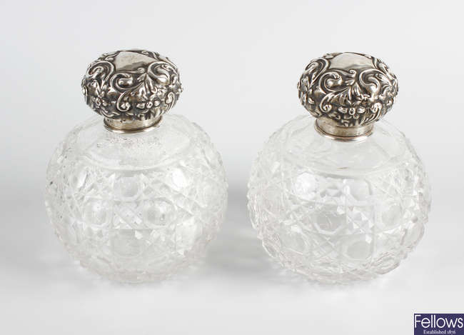 A pair of early 20th century hallmarked silver topped cut glass scent bottles