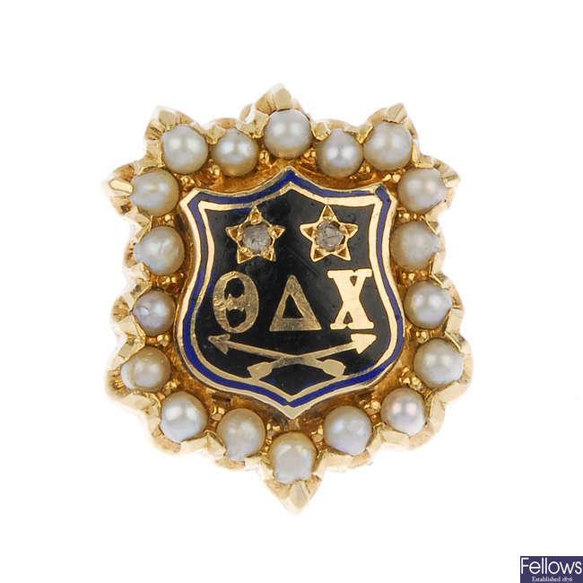An early 20th century gold diamond, split pearl and enamel 'Theta Delta Chi' fraternity pin.