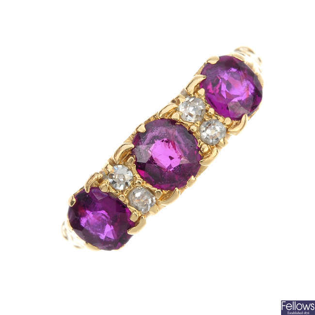 An early 20th century 18ct gold ruby three-stone and diamond accent ring.