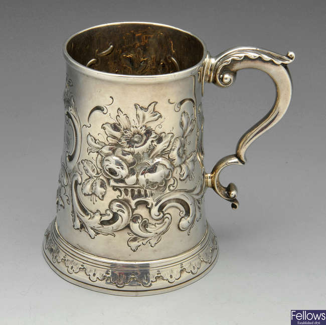 A George III silver mug with embossed decoration.