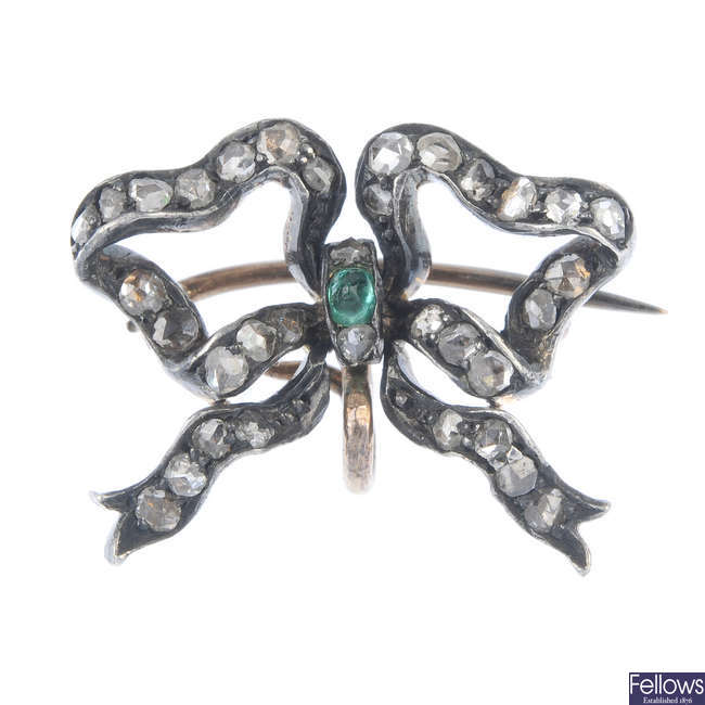 An early 20th century silver and 15ct gold, emerald and diamond bow brooch.