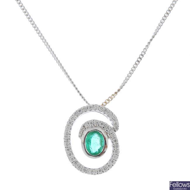 An emerald and diamond pendant.