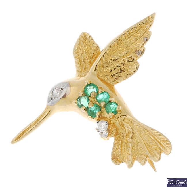 An emerald and diamond hummingbird brooch.