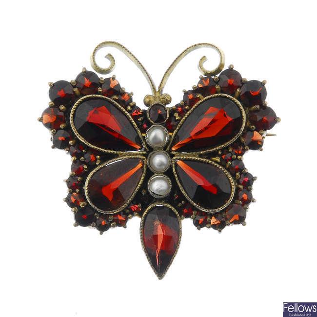 A garnet and split pearl butterfly brooch.