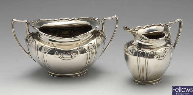 An Art Nouveau silver sugar bowl and cream jug, etc.