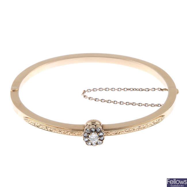 An early 20th century gold diamond hinged bangle.