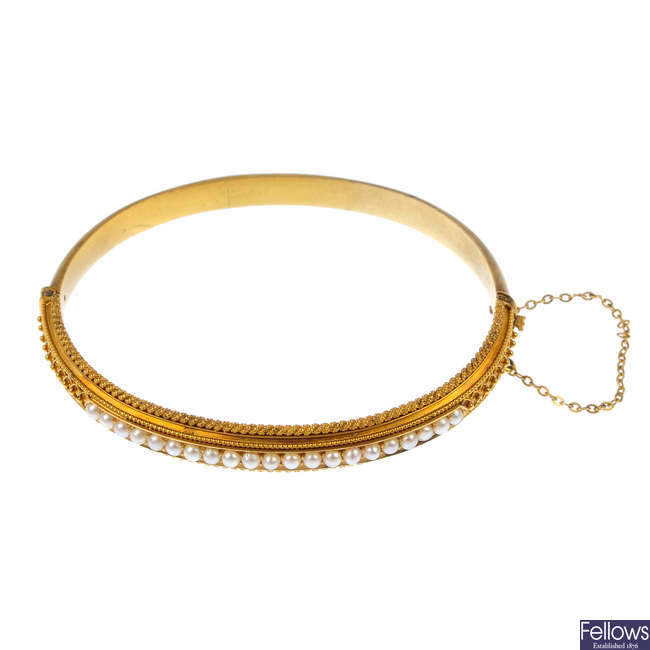 A late 19th century gold split pearl hinged bangle.
