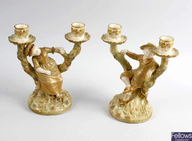 A pair of James Hadley Royal Worcester candlesticks, plus four figures.