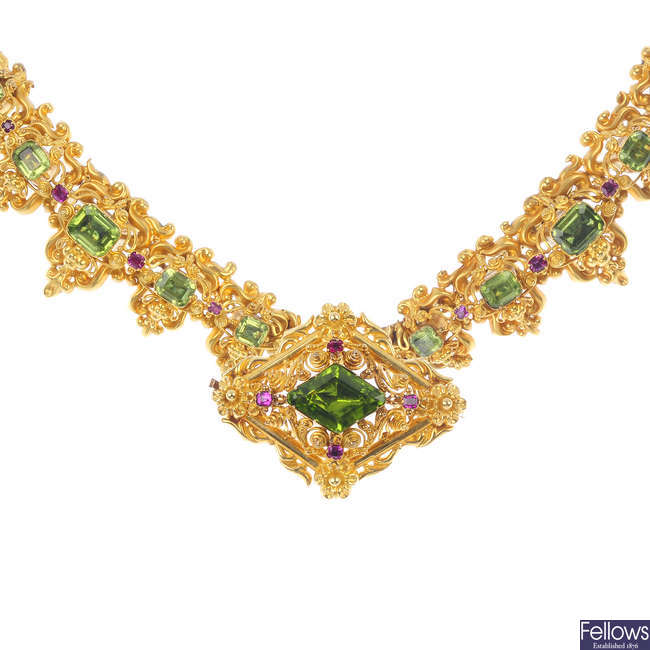 An early 20th century gold peridot and ruby necklace and a brooch.