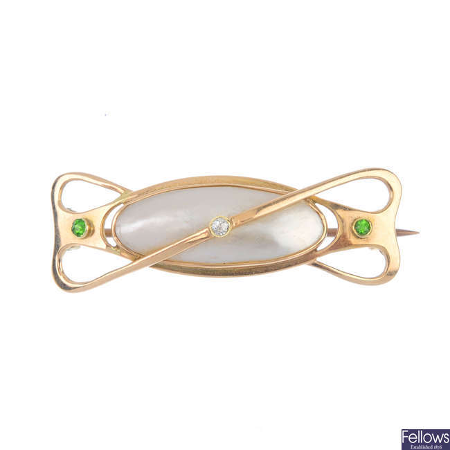 An early 20th century 15ct gold mother-of-pearl, diamond and demantoid garnet brooch.