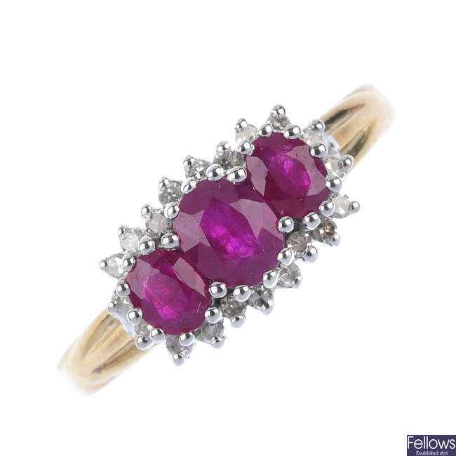 A 9ct gold ruby three-stone and diamond cluster ring.