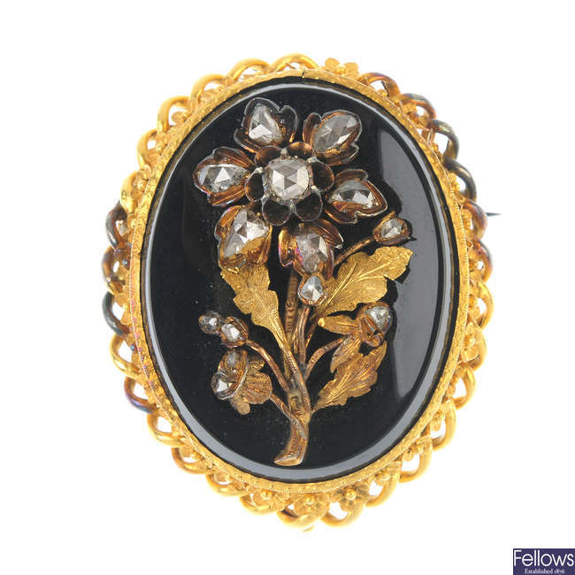 A late Victorian gold onyx and diamond brooch.