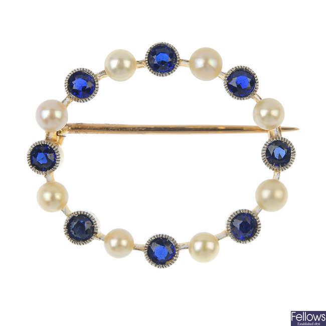 An early 20th century gold sapphire and seed pearl wreath brooch.