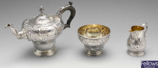 A George II silver cream jug, plus a sugar bowl and teapot.