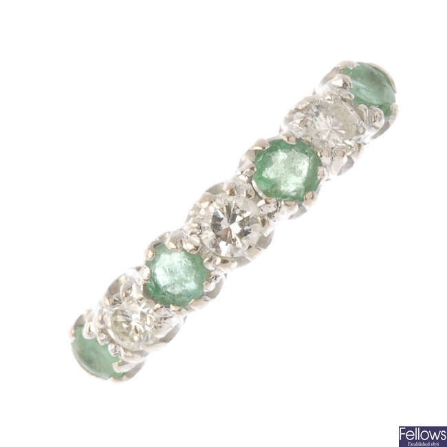 An 18ct gold emerald and diamond half-circle eternity ring.