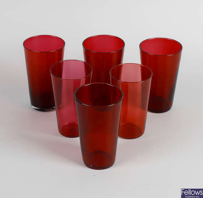 A collection of assorted cranberry glass items,