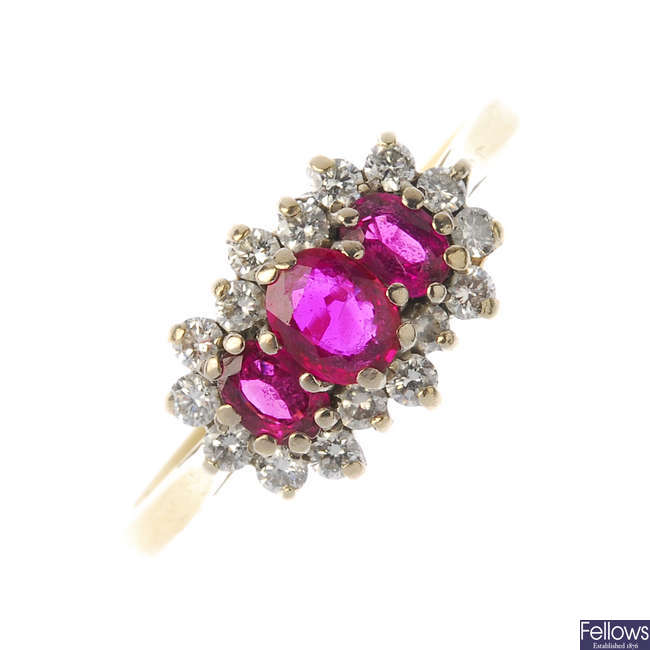 An 18ct gold ruby three-stone and diamond cluster ring.