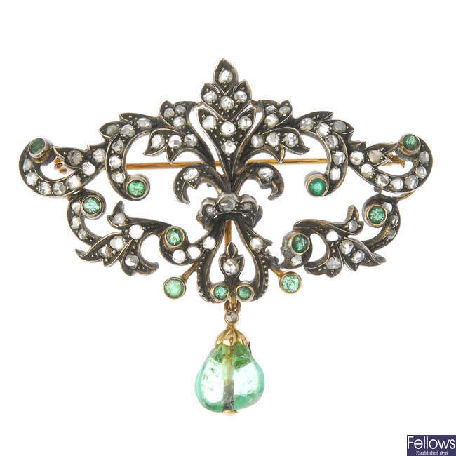 A diamond and emerald brooch.
