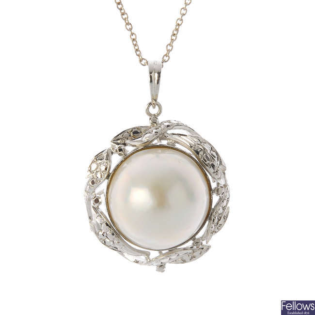 A mabe pearl pendant and earrings.