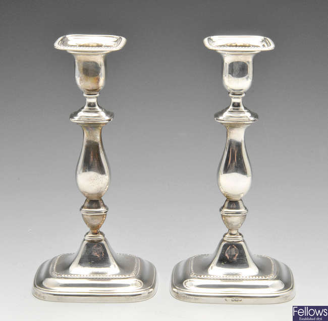 A pair of turn of the century silver mounted candlesticks.
