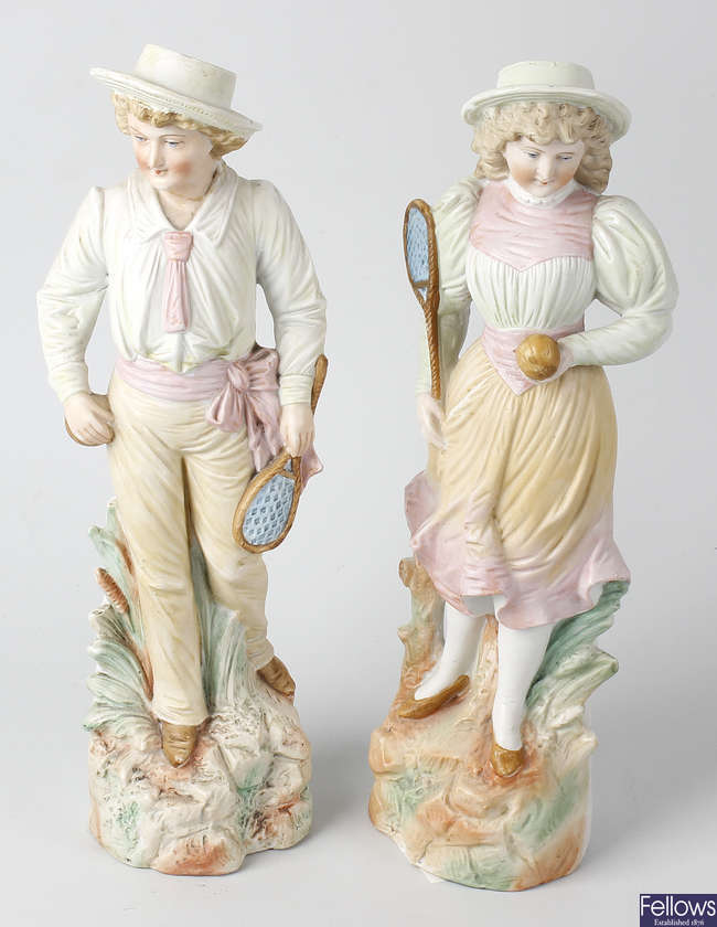 A pair of bisque figures, together with a pair of candlesticks.