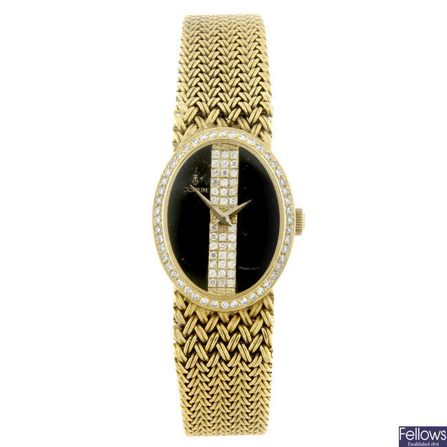 CORUM - a lady's yellow metal bracelet watch.