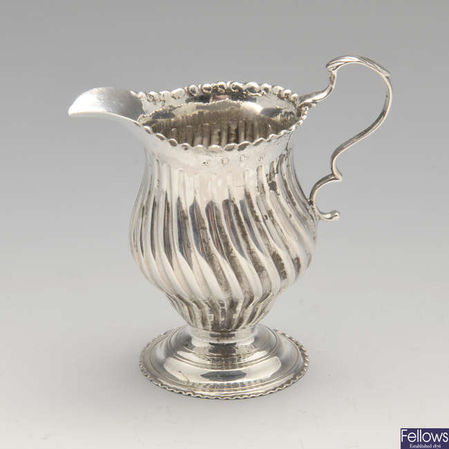 A Georgian silver cream jug, plus a cased 1920's silver mounted clothes bush and comb set.