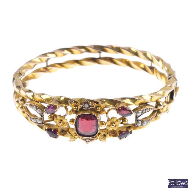 An Edwardian 9ct gold garnet and split pearl hinged bangle.