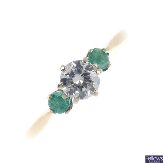 A diamond and emerald three-stone ring.