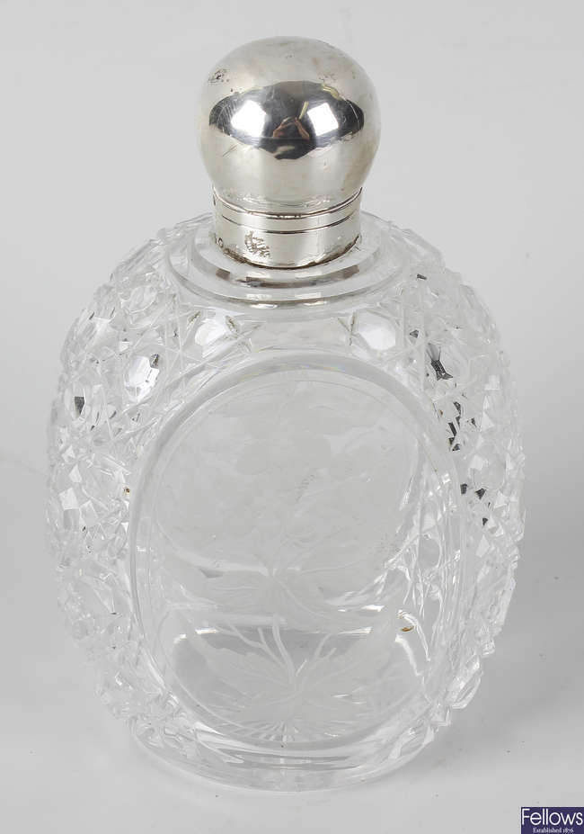 A cut glass flask, with oval panels to front and back, with etched decoration of flowers.