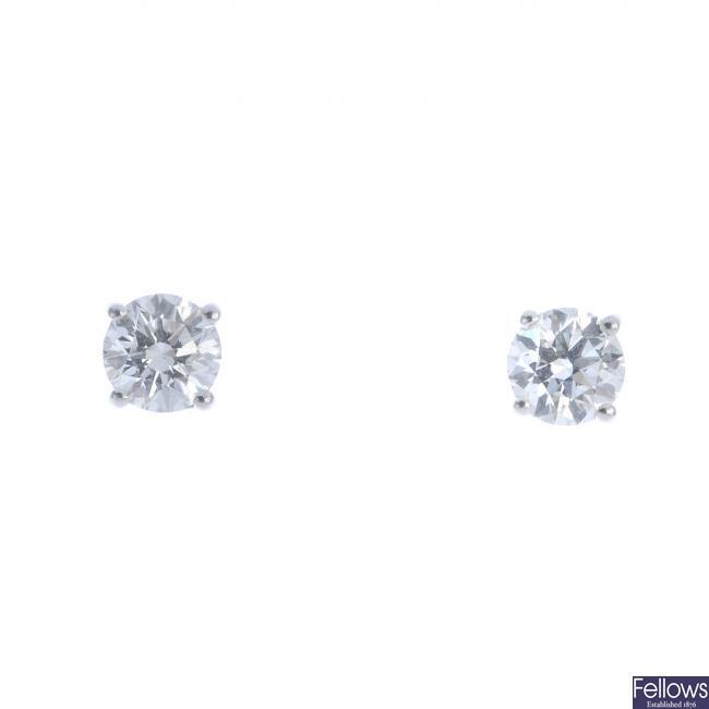 A pair of platinum brilliant-cut diamond single-stone earrings.