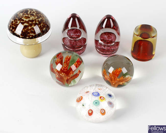 A group of seven glass paperweights.