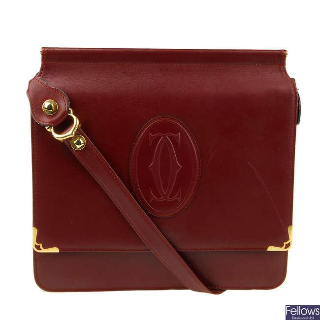 CARTIER - a reversible Bordeaux messenger handbag.