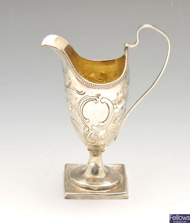 A George III silver helmet cream jug & an Indian Colonial silver pepper pot.