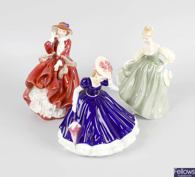 A group of nine Royal Doulton figurines.