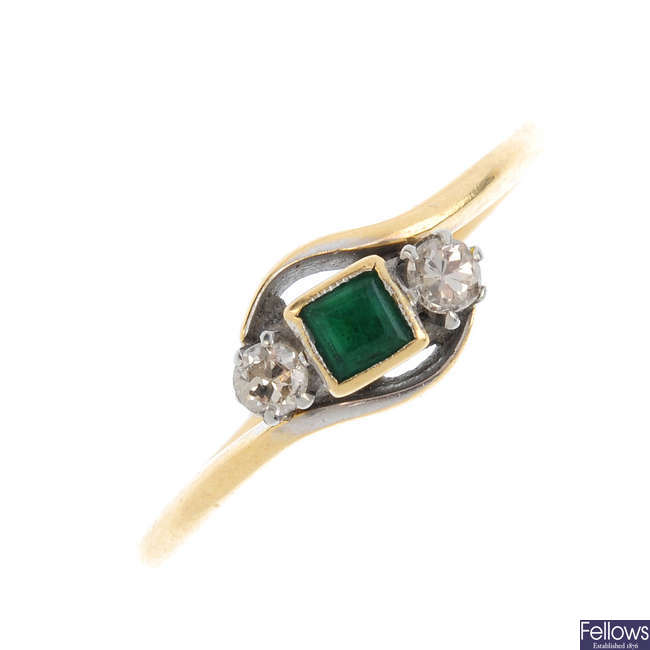 An emerald and diamond three-stone crossover ring.