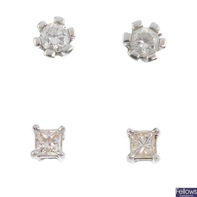 Two pairs of diamond stud earrings.
