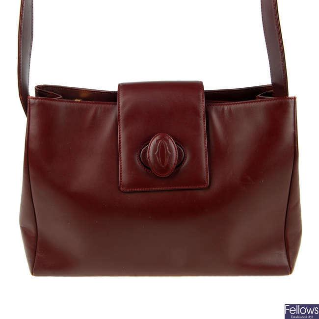 CARTIER - a Bordeaux leather handbag.