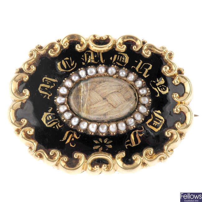 A mid Victorian enamel and split pearl mourning brooch.